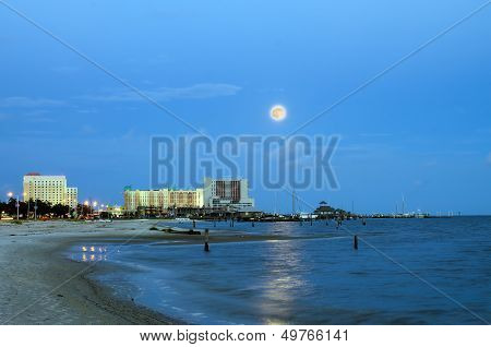 Biloxi, Mississippi, casinos and buildings along Gulf Coast shore in night image with rising moon