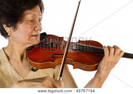 Senior Woman Concentrating While Playing The Violin