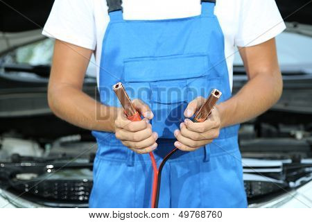Young driver with battery jumper cables to charge dead battery
