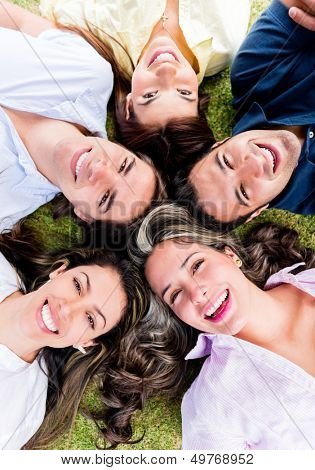 Circle of friends lying on the floor at the park