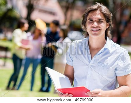 Happy university student at the campus with a notebook