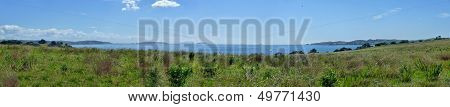 Panoramic View Over Meadows With Bushes In Front Of The Sea Behind
