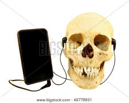 Human skull listening music with earphones on a mobile phone