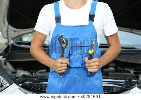 Young car mechanic repairing car