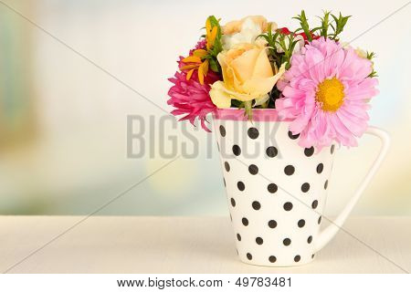 Beautiful bouquet of bright flowers in color mug, on wooden table, on bright background