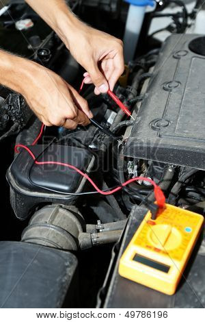 Auto mechanic uses multimeter voltmeter to check voltage level in car battery