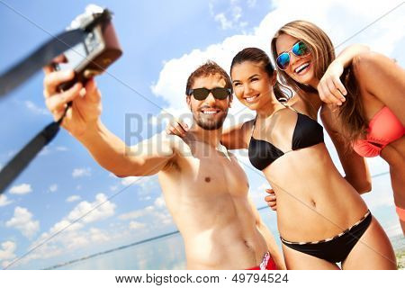 Portrait of happy friends taking photo of themselves on the beach