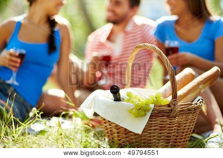 Basket with bottle, grapes and baguettes on background of group of friends