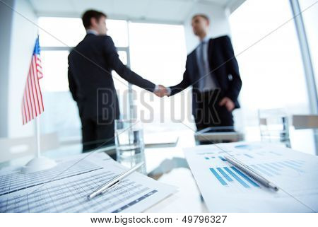 Image of business documents and pens on workplace with two employees handshaking on background