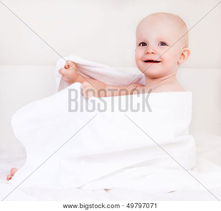 cute baby girl with a white towel after bath in bed at home