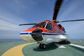 stock photo of helicopter  - The S92 helicopter park on oil rig to pick up worker - JPG
