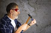 stock photo of gad  - Construction worker wears safety glasses and holds hammer and gad tool - JPG