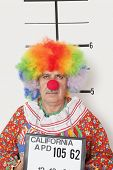foto of mug shot  - Portrait of senior clown posing for mug shot - JPG