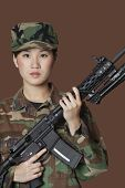 stock photo of corps  - Portrait of beautiful young US Marine Corps soldier with M4 assault rifle over brown background - JPG