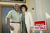 Portrait of smiling African American couple standing by sold real estate sign