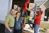 stock photo of baby delivery  - Happy couple with delivery men unloading moving boxes from truck into new house - JPG