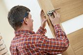 stock photo of locksmith  - Male worker handyman carpenter at lock installation into wood door - JPG