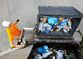 stock photo of municipal  - Worker of urban municipal recycling garbage collector truck loading waste and trash bin - JPG