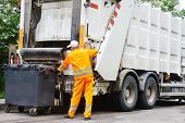 stock photo of recycling bin  - Worker of urban municipal recycling garbage collector truck loading waste and trash bin - JPG
