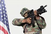 image of m4  - US Marine Corps soldier aiming M4 assault rifle with American flag against gray background - JPG