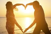 stock photo of love making  - Couple making romantic heart shape at sunrise on the beach - JPG
