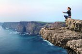 pic of cliffs moher  - Woman at meditation on the edge of cliff - JPG