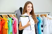 stock photo of dress mannequin  - Beautiful young stylist near rack with hangers - JPG