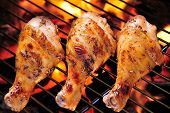 stock photo of charcoal  - Grilled chicken Legs on the  flaming grill - JPG