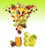Diffferent fruits and berries falls into glass of fresh juice, on green background