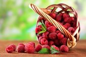 stock photo of wooden basket  - Ripe sweet raspberries in basket on wooden table - JPG