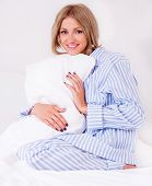beautiful young woman wearing pajamas in bed at home