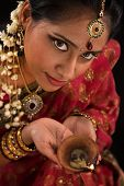 stock photo of sari  - Close up portrait of beautiful young Indian woman in traditional sari dress holding a diwali oil lamp light - JPG