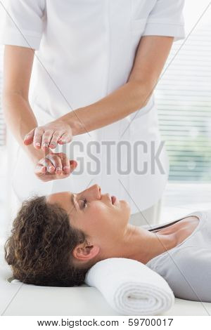 Female therapist performing Reiki over woman at spa