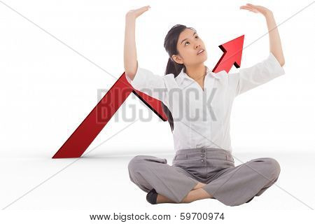 Businesswoman sitting cross legged pushing up against red arrow pointing up