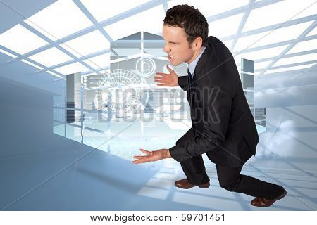 Businessman posing with arms out against room with holographic cloud