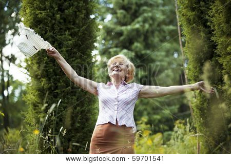 Freedom. Happy Old Lady With Hut Smiling In The Garden. Lifestyle
