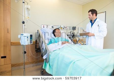 Young doctor looking at patient while writing notes on clipboard in hospital room