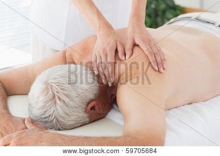 Female massage therapist massaging back of senior man in medical office