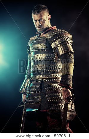 Portrait of a courageous ancient warrior in armour with sword.