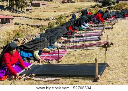 PUNO, PERU - JULY 25, 2013: women weaving in the peruvian Andes at Taquile Island