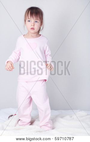Little girl jumping on bed on wall background