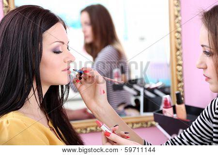 Young woman stylist doing makeup beautiful girl in beauty salon