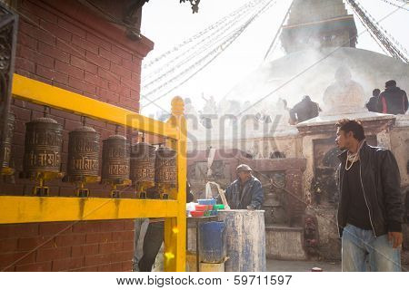 KHATMANDU, NEPAL - DEC 17, 2013: Unidentified man sell cement for donations for repairs near stupa Boudhanath during festive solemn Puja of H.H. Drubwang Padma Norbu Rinpoche's reincarnation's.