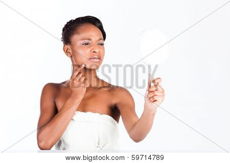 Young African woman in Studio doing body care and checking her face for pimples and spots with mirror for young and beautiful skin