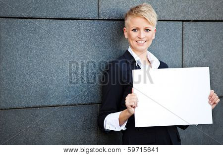 Attractive businesswoman holding blank white sign