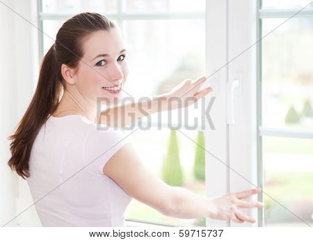 Attractive young woman shuts window