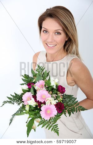 Happy woman holding bunch of flowers