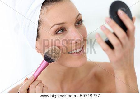 Smiling woman in bathroom applying makeup on