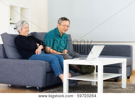 Asia old couple watching on computer at home