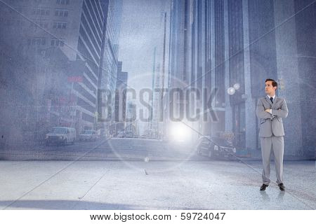 Serious businessman with arms crossed against urban projection on wall